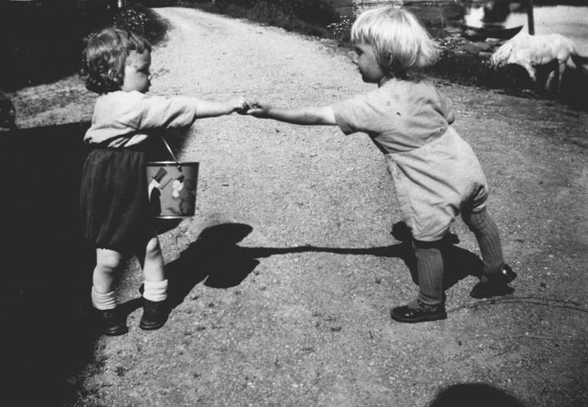 To små barn som leker sammen på en vei, ene har et lekespann.