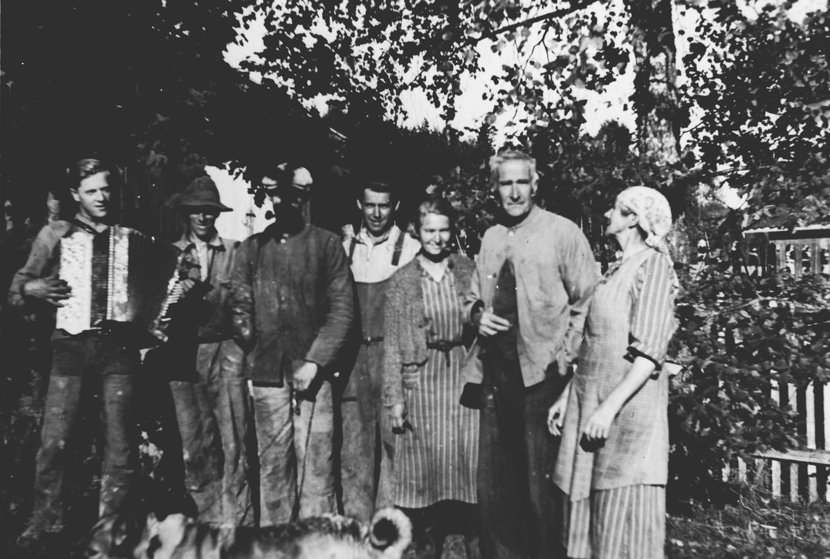 7 personer + 1 hund fotografert på gardstun. Mann med trekkspill