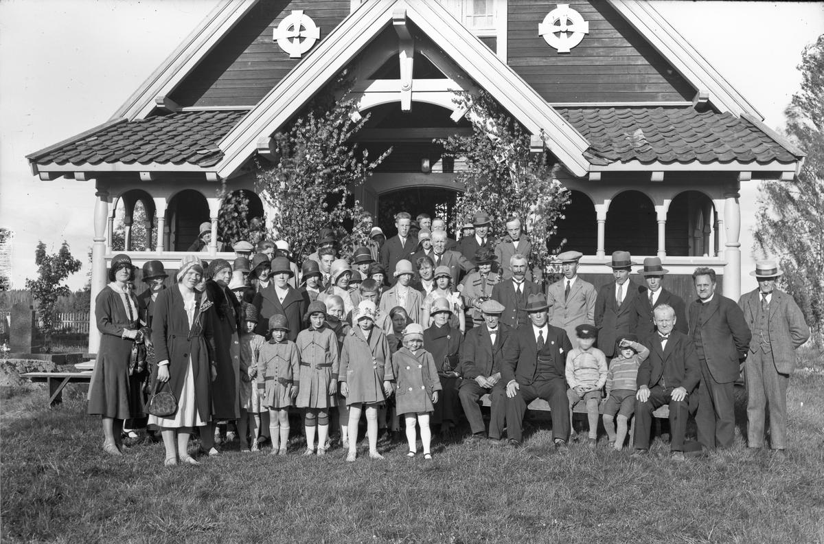 Forsamling voksne og barn utenfor et forsamlingslokale eller en kirke. Kirkegård til venstre.