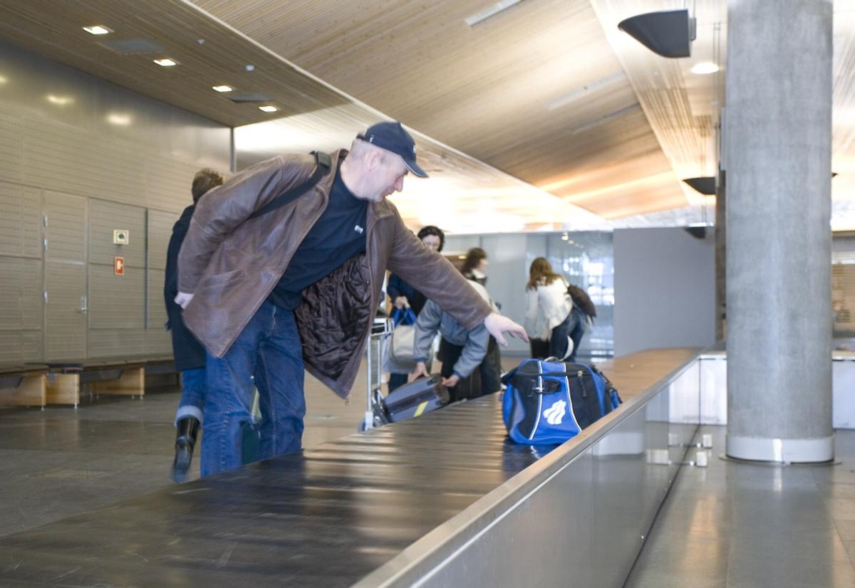 Vesker. Bagasjeutlevering innland. En mannlig reisende tar bagasje fra bagasjebåndet. Fotodokumentasjon i forbindelse med dokumentasjonsprosjekt - Veskeprosjektet 2006 - ved Akershusmuseet/Ullensaker Museum.