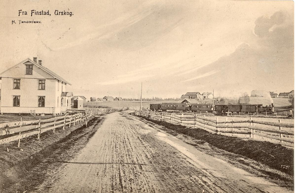 Tog retning Sørumsand står på Finstadbru stasjon. Brødrene Borstads landhandel til venstre.