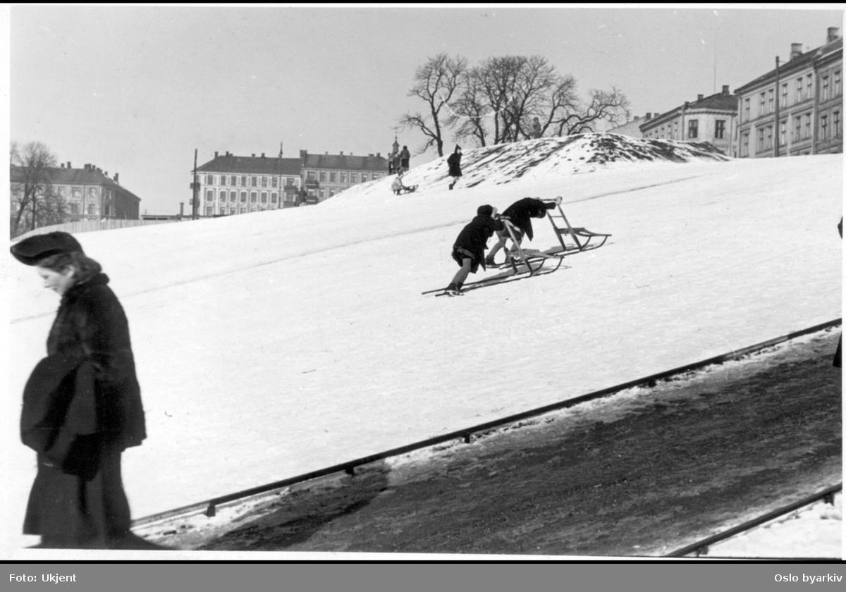 Grünerhagen en vinterdag, sett fra Nordre gate, hvor den sydlige delen av parken skråner ned mot Akerselva og brukes til aking om vinteren. Barn med kjelke og sparkstøttinger. Vinterkledd dame ned gangveien. Høyre hjørne i bildet, bygårdene i Fossveien. Venstre midt i ses bygårdene i Marselis' gate 26, 27 og Fossveien 10.