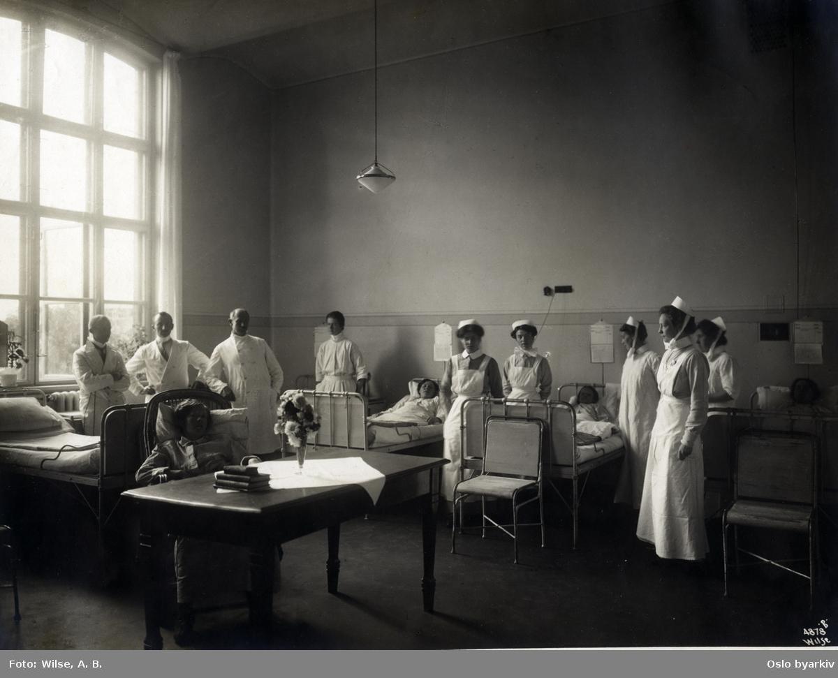 Legevisitt på pasientværelse på Ullevål sykehus. Leger og sykepleiersker. Bilde brukt i kommuneberetningen fra 1887 - 1911.