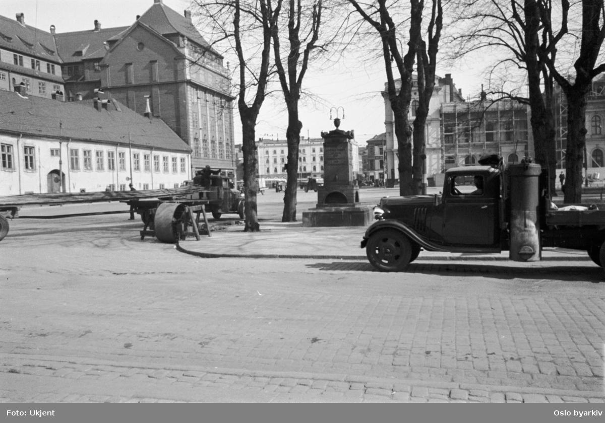 Kristian Frederiks plass med Paléhagen. Strandgata mot Østbanen. Havnegata nærmest. Paleét til venstre. Minnesmerke over Mathia Anker (Bernt Ankers hustru), laget av C.F. Stanley (avduket 1803). Reist i Paléhagen, senere flyttet til nordsiden av Oslo Bymuseum. Lastebil med knottbeholder.