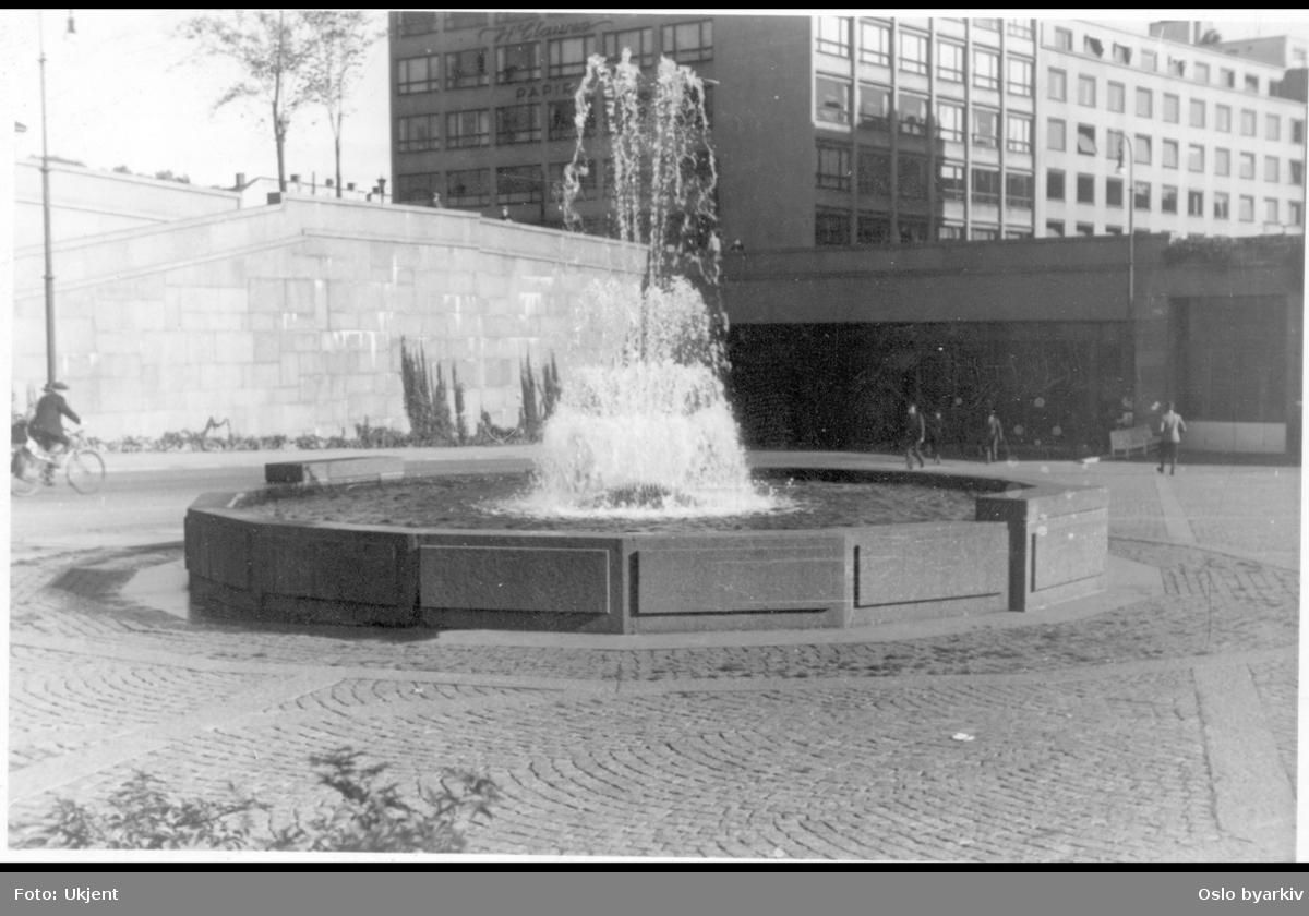 Arne Garborgs plass brosteinsbelagt og med fontene. Muren langs daværende Henrik Ibsens gate (Hammersborggata) mot garasjeanlegget til Hovedbrannstasjonen. Over Grubbegata med bruvelvet.Bakgrunnen Grubbegata 14, Clausengården (dengang Henrik Ibsens gate 5).