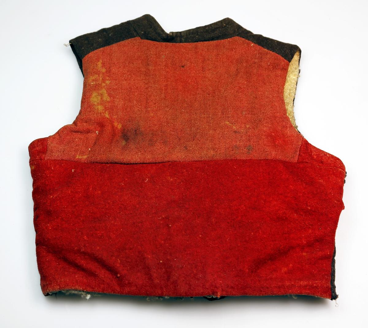 Vest i grovt ullstoff, med brun front og rød rygg, saueskinn til fôr, to lommer, metallknapper med messing overflate, en sekundær knapp nederst av plast.  Ryggstykket består av to store stoffbiter og to små under armene.