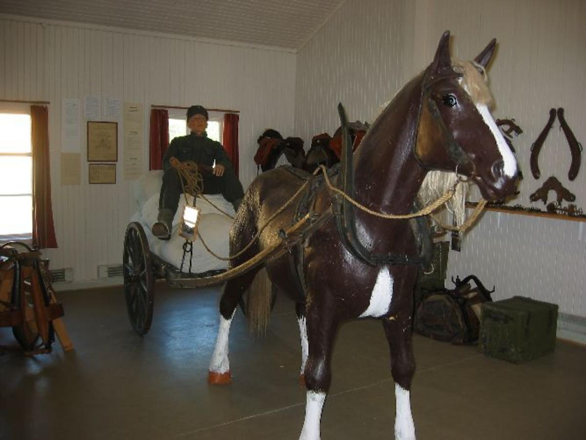 Modell i full størrelse av soldat, hest og vogn