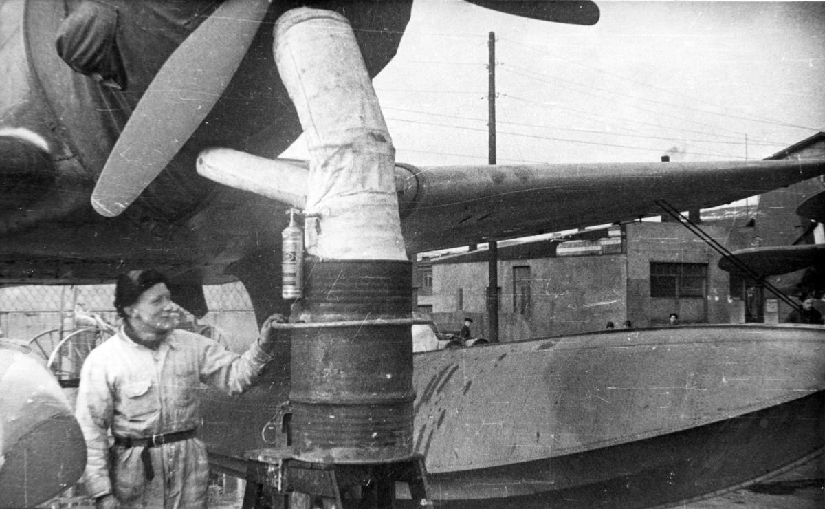 Et av 330 skvadronens Northrop fly på Island får motoren varmet opp av en mekaniker.