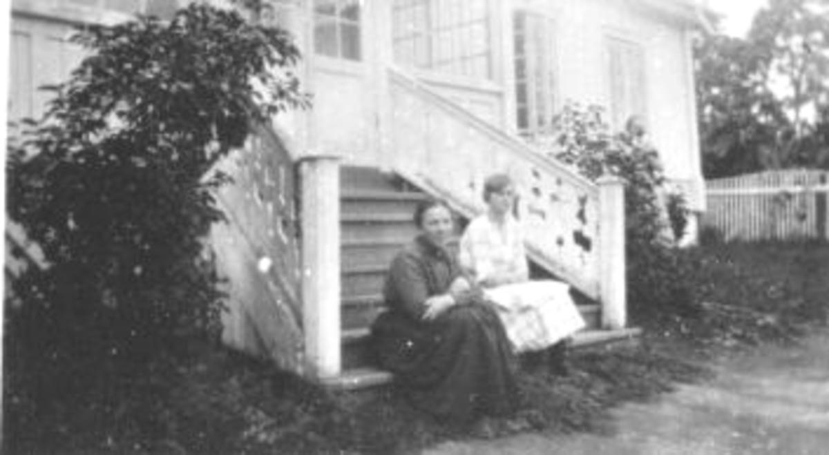 2 damer sitter i trappa foran hovedbygningen på Eik, Helgøya. Til Venstre Ida Sophie Stabo Eeg (1887-1958):