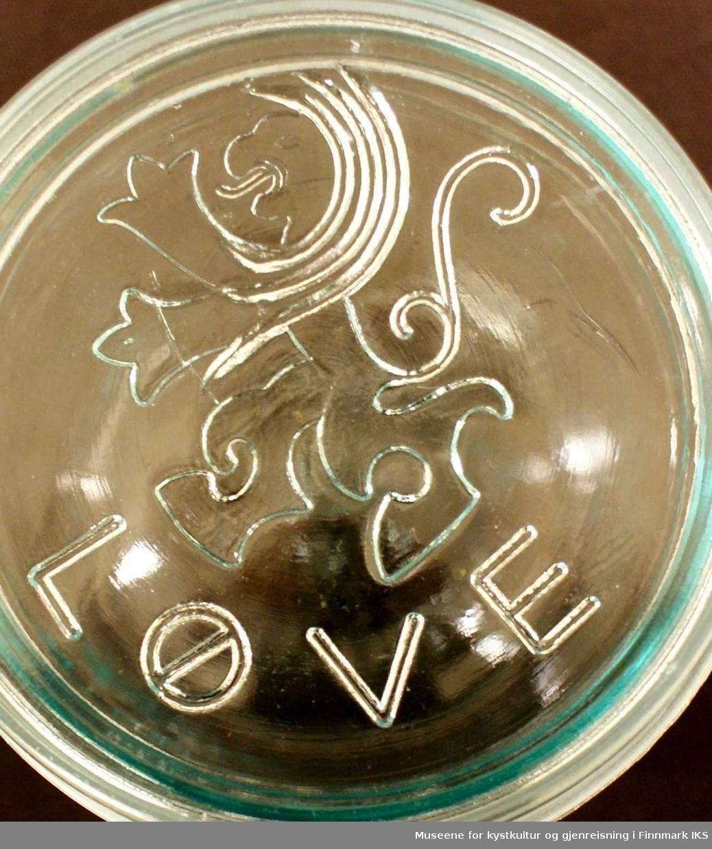 Både på lokket og på fremsiden av glasskrukken er detavbildet en stilisert løve. Løven står på bakbena og rekker frembena fremfor seg. Den er formet direkte i glasset, og er derfor blank. I bunnen av glasskrukken er det avbildet en lykt sammen med bokstavene DG, og dette er sannsynligvis logoen til Drammens Glass.