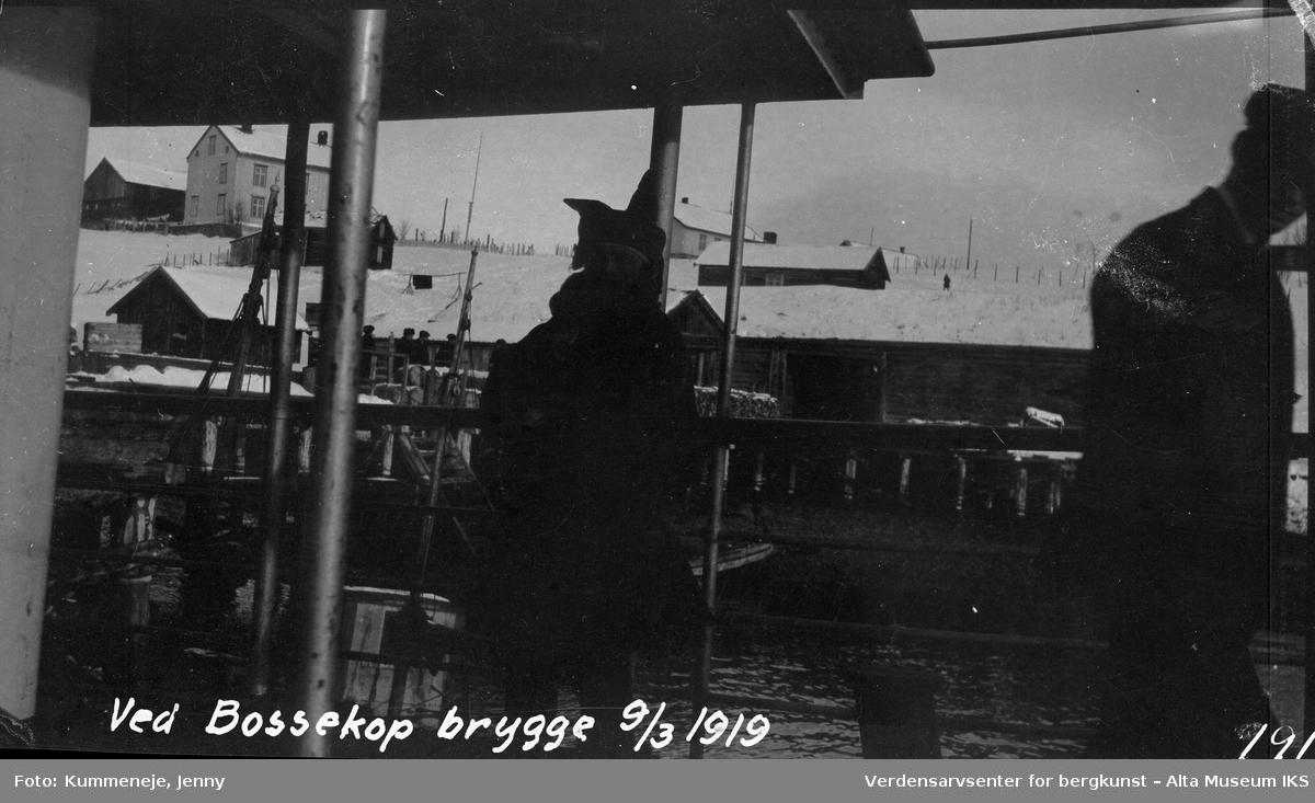 Mennesker i båt ved Bossekop brygge. Boliger i bakgrunn, 1919.