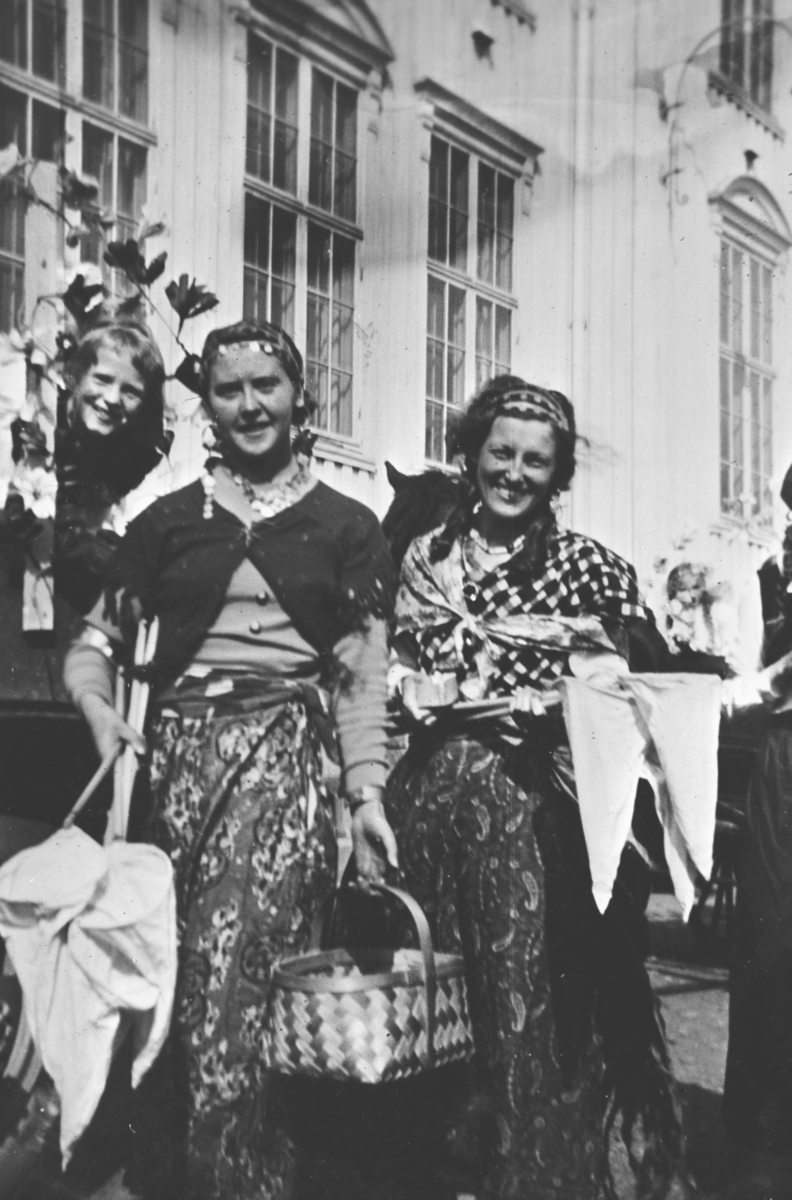 Damer i kostymer med håver og kurv foran hus. Margit Sundelin i midten. De to andre er ukjent.