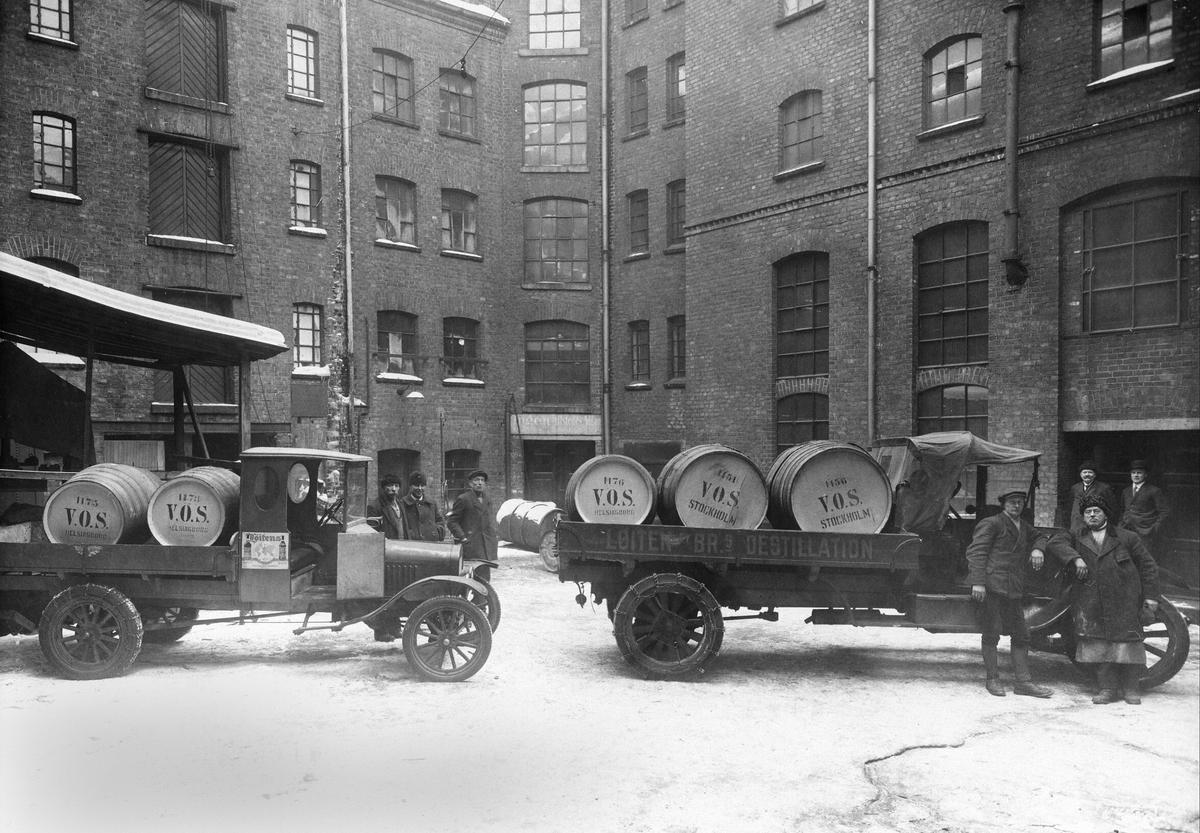 RP. LØITEN BRENNERI. OSLO. LASTEBILER LASTET MED BRENNEVINSFAT. CA. 1915-20. Lastebiler fra Løitens Br. s Destillasjon. Et tonns Ford TT til venstre. Produksjonen av den startet ikke før i 1917. Ukjent, større bil til høyre.
