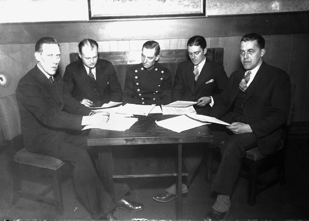 5 menn rundt et bord