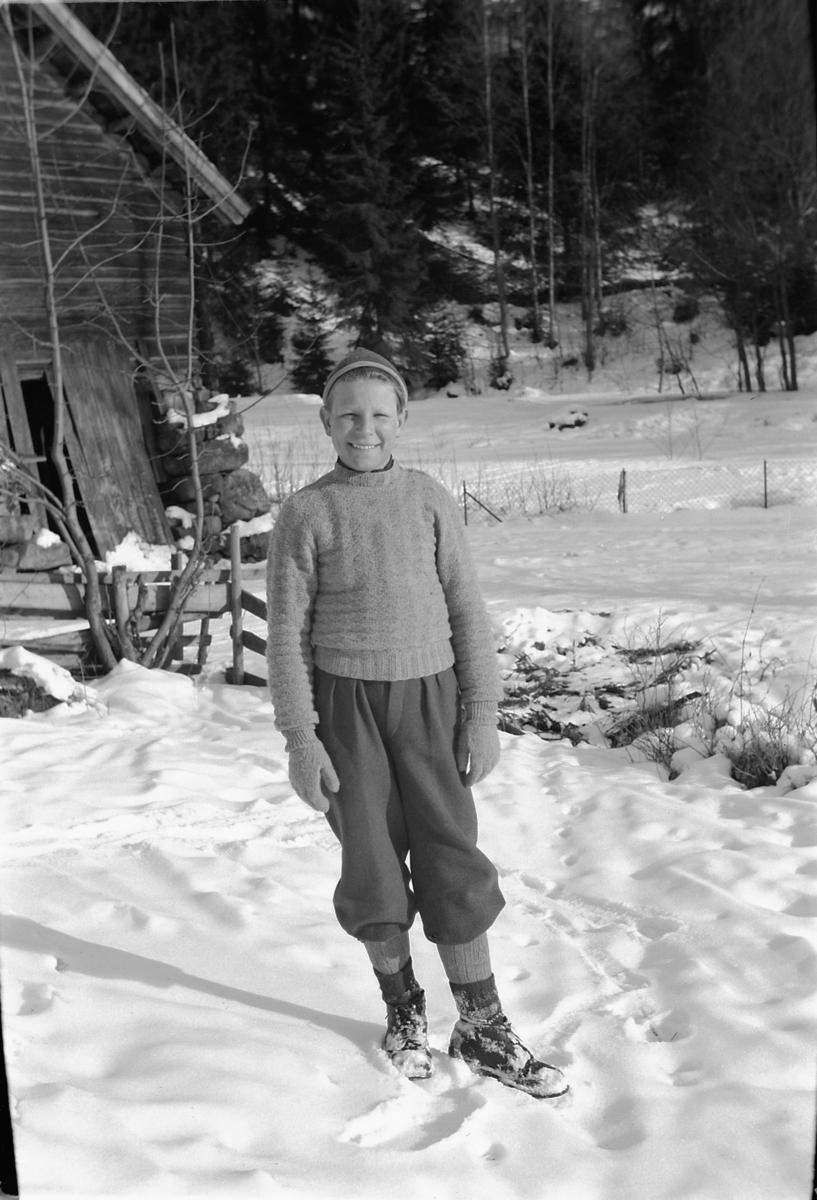 Eksteriør, vinter. Ukjent gutt foran et hus.
