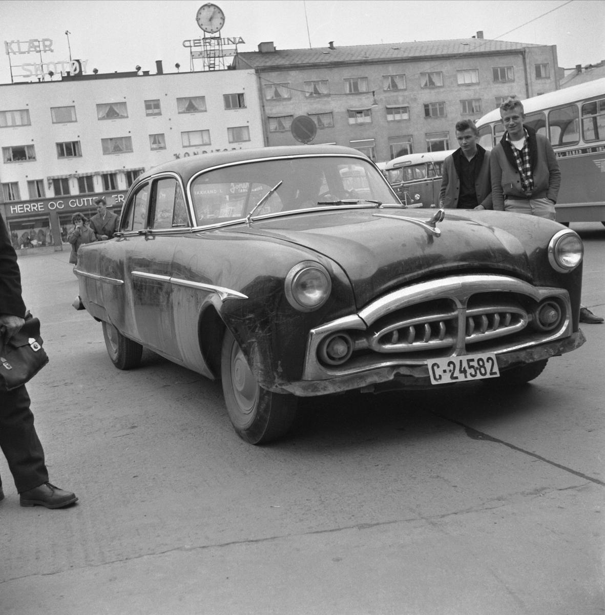 """""""DOLLARGLIS"""" C-24582 PÅ ØSTRE TORG, HAMAR. KNUT LANGDALEN OG GUNNAR JENSEN BEUNDRER BILEN. SE BOKA PÅ ET HUNDREDELS SEKUND, LØTEN OG OMEGN 1957-1964 I ORD OG BILDER AV HELGE REISTAD S. 225.  Bilen er en Packard årsmodell 1952-54."""