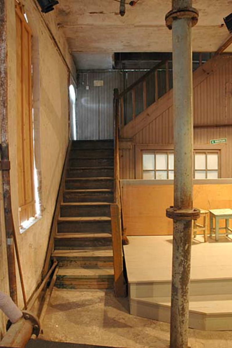 """Interiør fra Klevfos Cellulose- & Papirfabrik i Løten i Hedmark, som siden 1986 har vært drevet som Klevfos industrimuseum.  Dette fotografiet er fra hollenderisalen.  Vi ser trappa opp mot limloftet i etasjen over, og vi ser de panelte treveggene og vinduet til formannskontoret.  Til venstre ser vi en teglmurt, pusset vegg der vindusåpningene var forblendet med trelemmer.  Vi skimter også et tak som var utført som kappehvelv av teglstein mellom stålskinner.  Til høyre i forgrunnen ser vi et vertikalt tilførselsrør til """"supermølla"""".  Bak dette røret, foran formannskontoret, ser vi en platting som er innsatt som scene for teaterforestillingen «Arbesdaer», som siden 1988 har vært framført i dette lokalet fem-seks ganger hver sesong.  Forestillingen handler om dagliglivet i og omkring fabrikken. Ådalsbruk."""