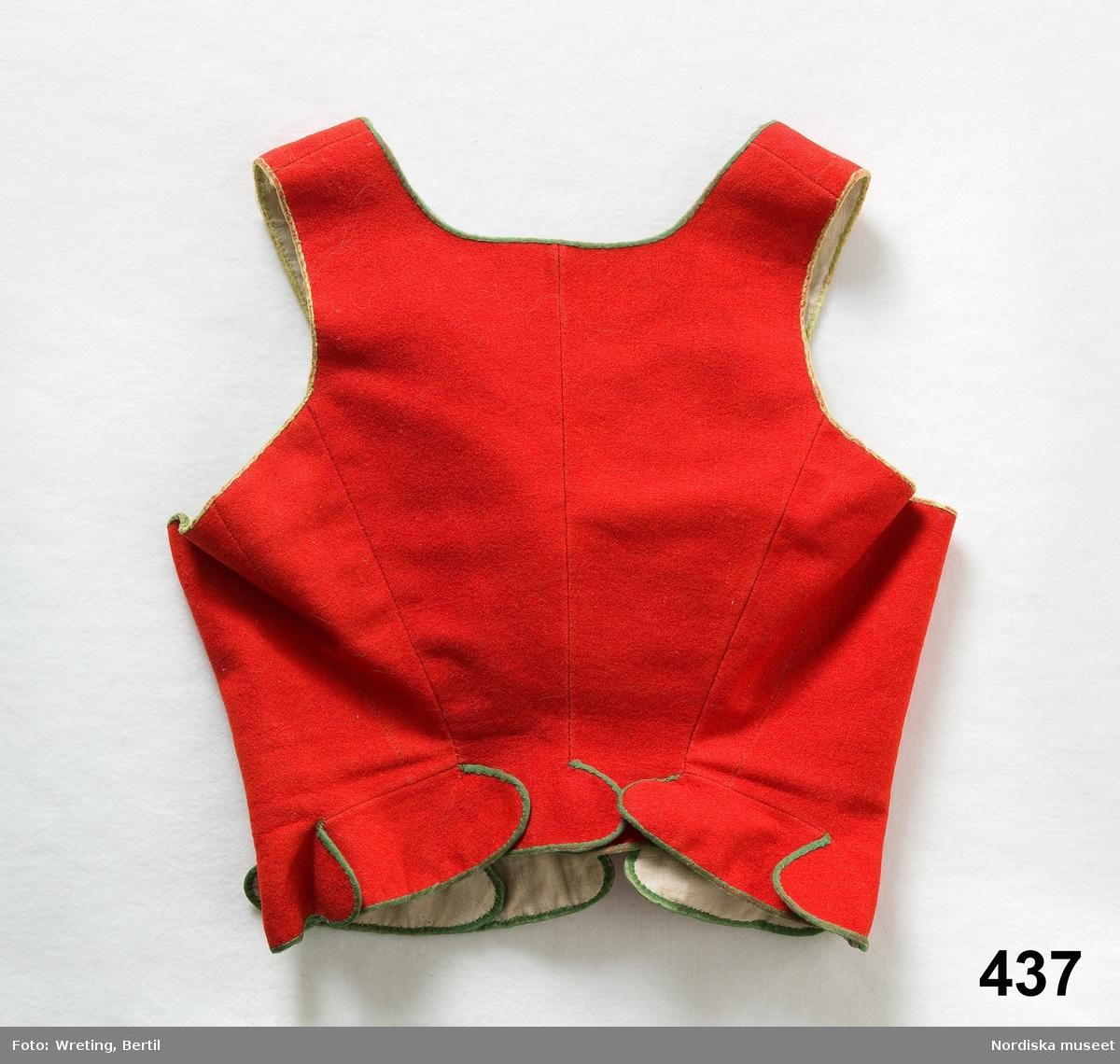 """Livstycke av rött kläde, 2 framstycken, 2 bakstycken, materialskarvar i sidorna. I nederkanten ett kort skört bestående av 10 öppna rundade flikar som överlappar varandra som fjäll. Kantat med gröna sidenband, foder av vit linnelärft, häktas fram med 7 hakar och hyskor av mässing.  Bilaga: """" Tillhörande den gamla Skedevidräkten. Finns ytterst få lämningar i behåll av denna dräkt, som varit lika även i Regna socken. Såg under min resa ej ett enda plagg mer än dem jag köpt.""""  ( pastorsadjunkt E. Blom 1873)  /Berit Eldvik 2006-09-14"""