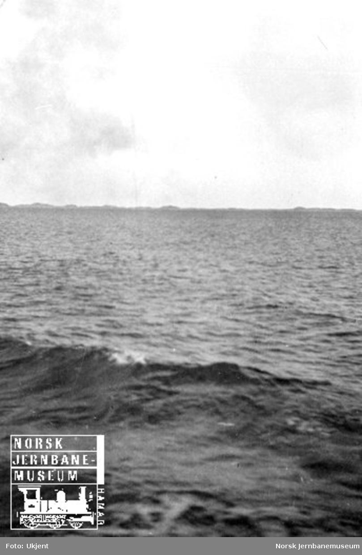 Motiv fra havet med en seilbåt i bakgrunnen