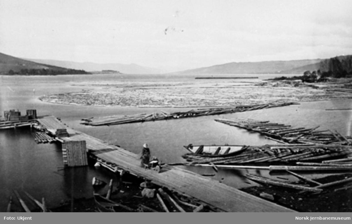 Brygge utenfor Hadeland glassverk med tømmerlenser i forgrunnen og utsikt mot Nøklebytangen