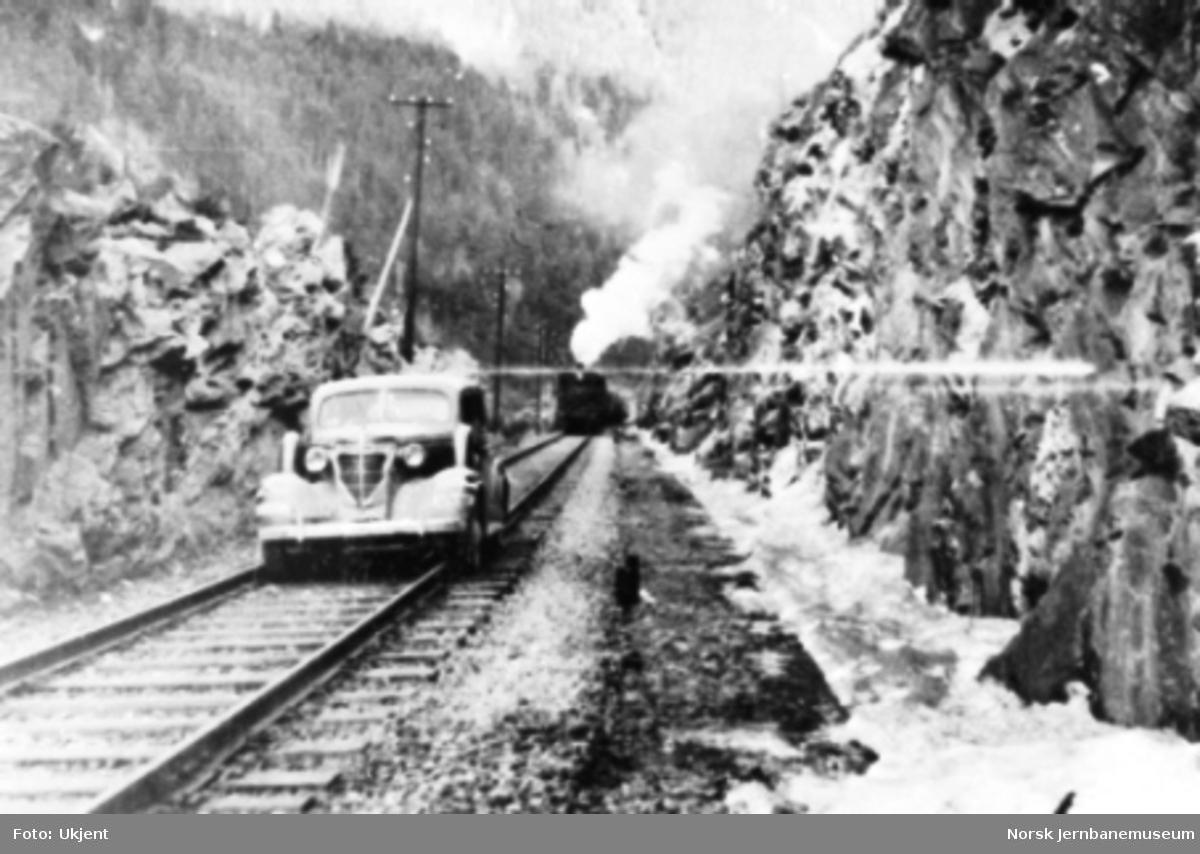 Personbil kjører på jernbanetraseen i Rosten; damptog i bakgrunnen