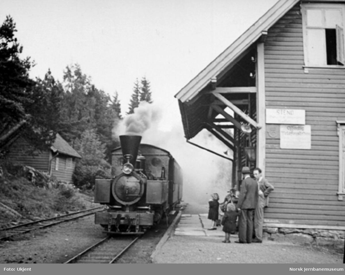"""Nesttun-Osbanens tog med damplokomotivet """"Os"""" ankommer Stend stasjon; reisende på plattformen"""