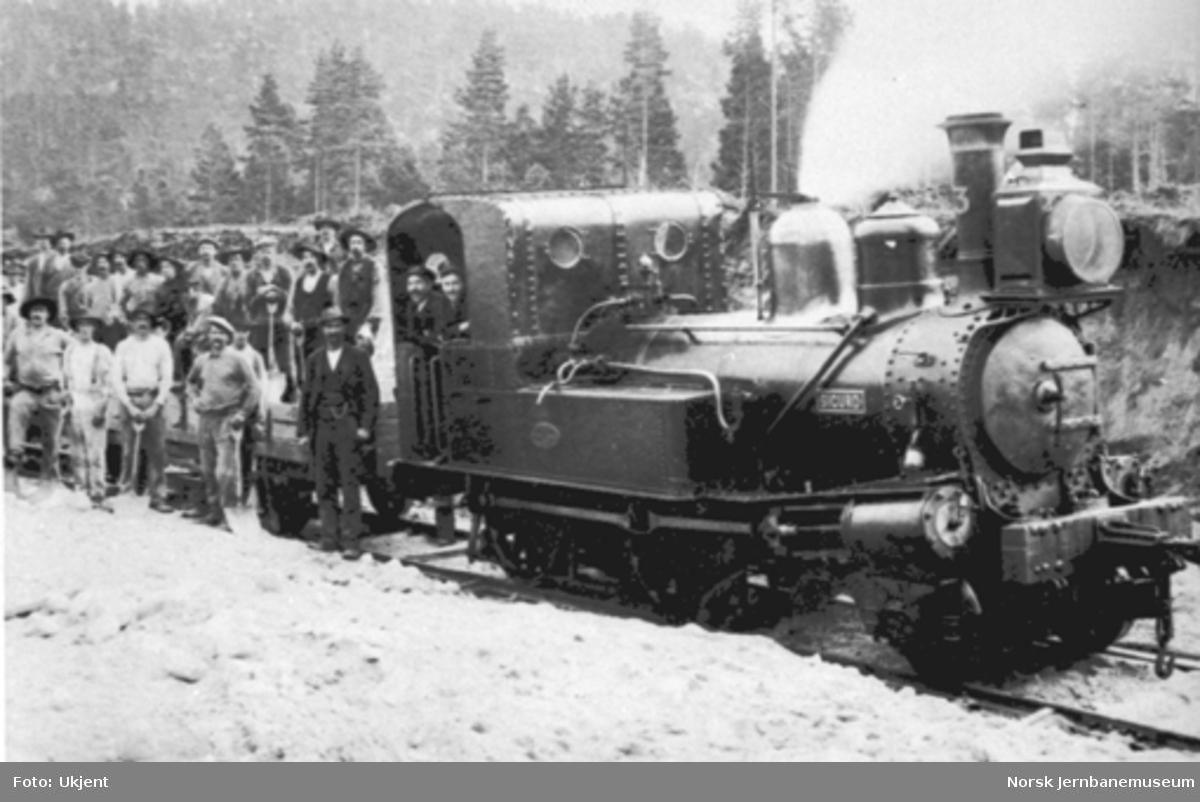 """Damplokomotiv type IV nr. 3 """"Sigurd"""" foran arbeidstog på Treungenbanen; anleggsarbeiderne poserer på første grusvogn"""
