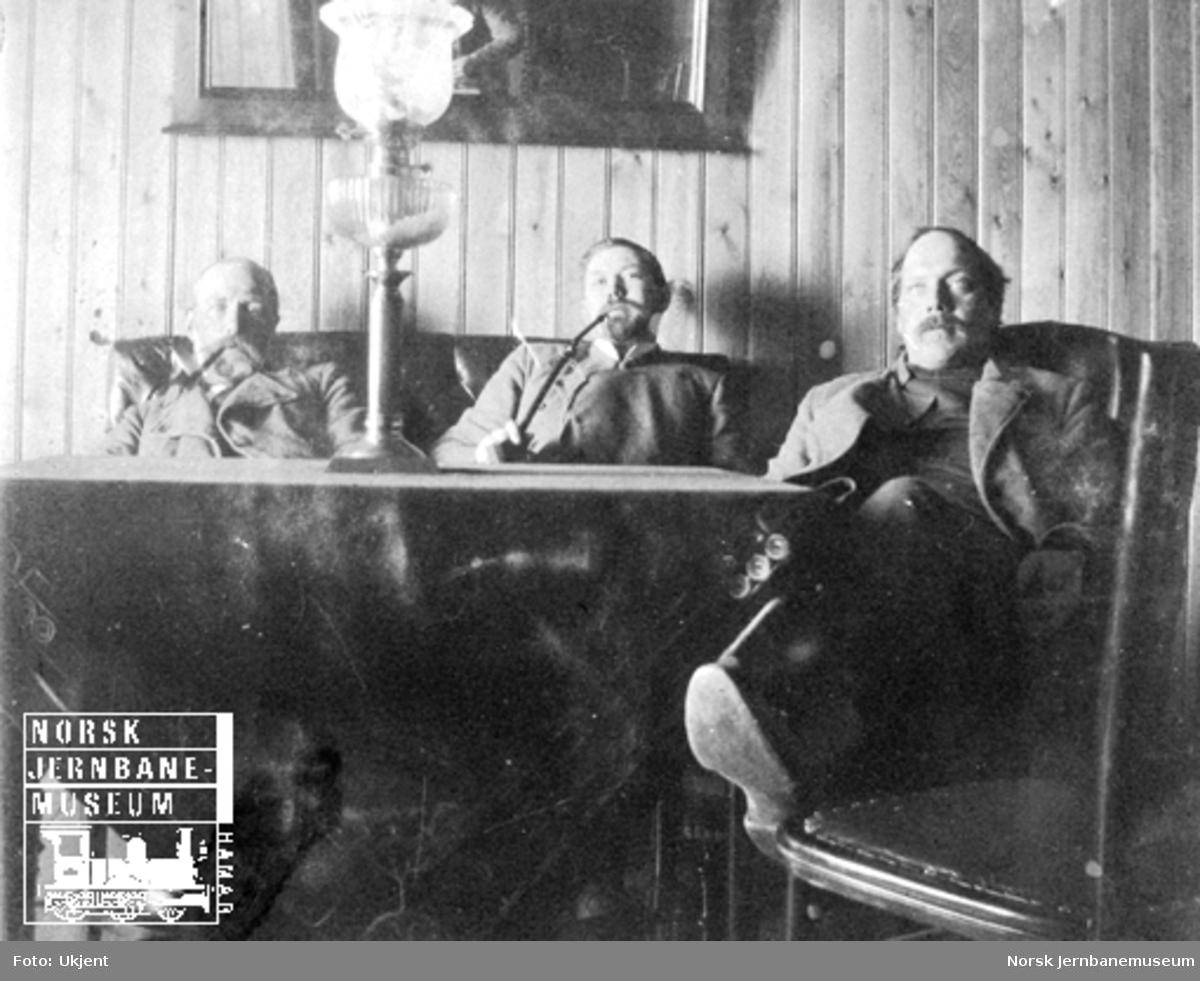 Tre menn i sosialt lag på disposisjonsværelset på Finse st.