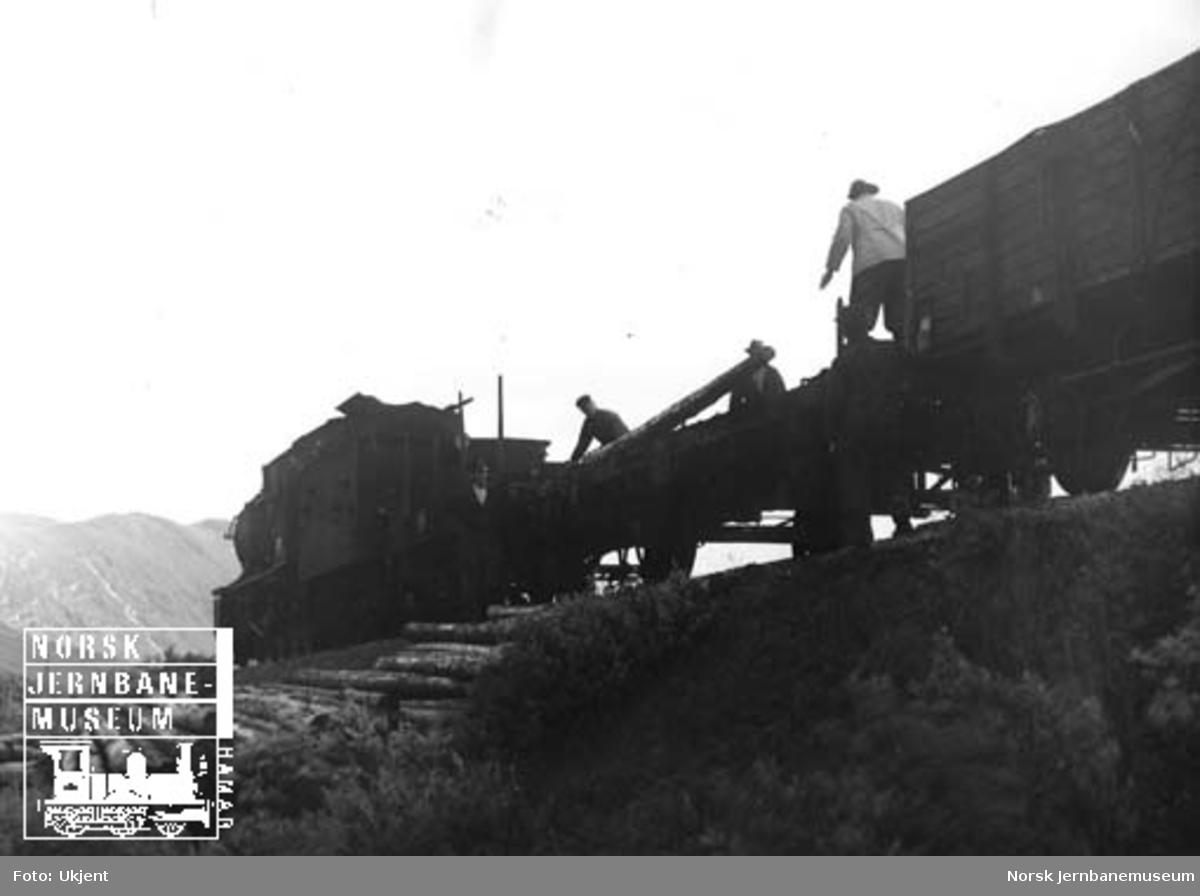 Lossing av tømmerstokker på fri linje på Bergensbanen, trolig til snøskjermer eller snøoverbygg