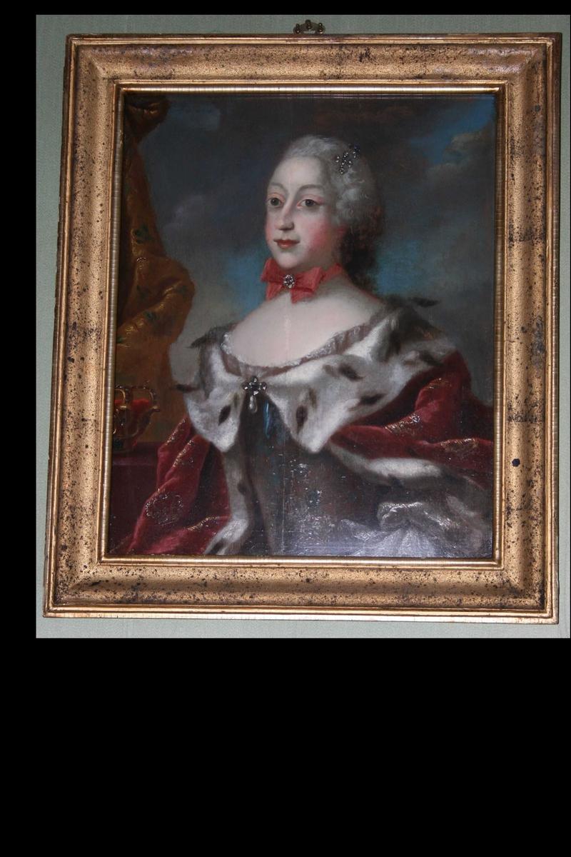 Portrett i halvfigur. Kvinne med parykk, rød kappe med hermelin. Rokokkodrakt. Rødt bånd med sløyfe rundt halsen. Krone i bakgrunnen.