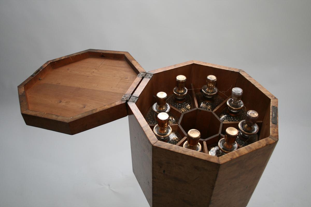 8-kantet kasse på lav søyle og tre bein. Hjul under beina.  Har 8 trapesformede rom med tilpassede karafler. 1 åttekantet rom i midten.