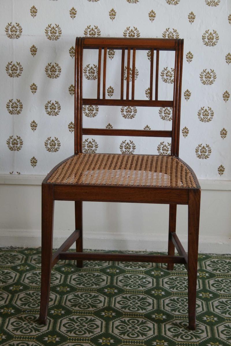 Spinkel stol i mahogni, med rottingsete, smale spiler i ryggen. 5 stoler og 1 kanapé