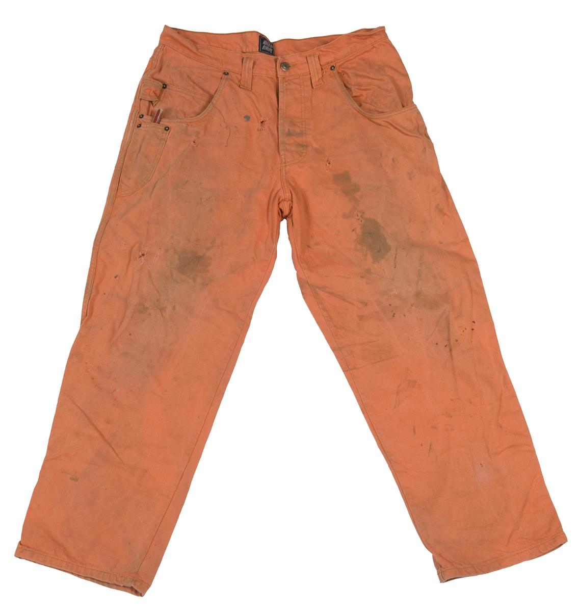Ensfarget jeans med knapper i gylfen. Flekker og hull. Ekstra verktøylomme og hempe.