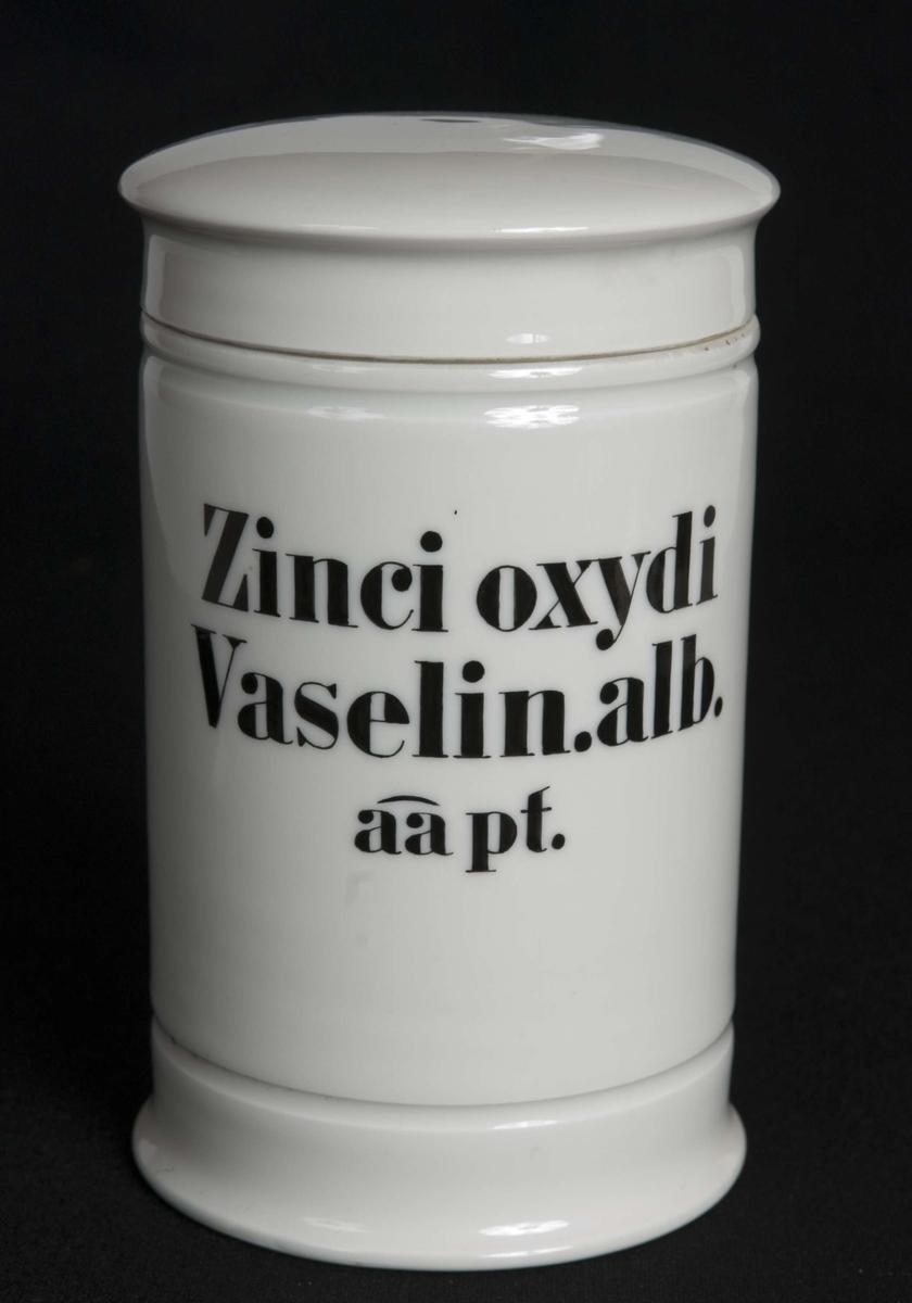 Standglass med lokk. Horisontale riller over og under sort påmalt skrift.