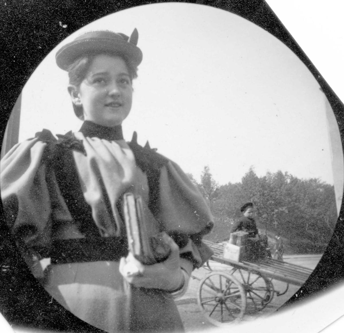 Kunstner Signe Hvistendahl med bok under armen. Kjerre med gutt i bakgrunnen.