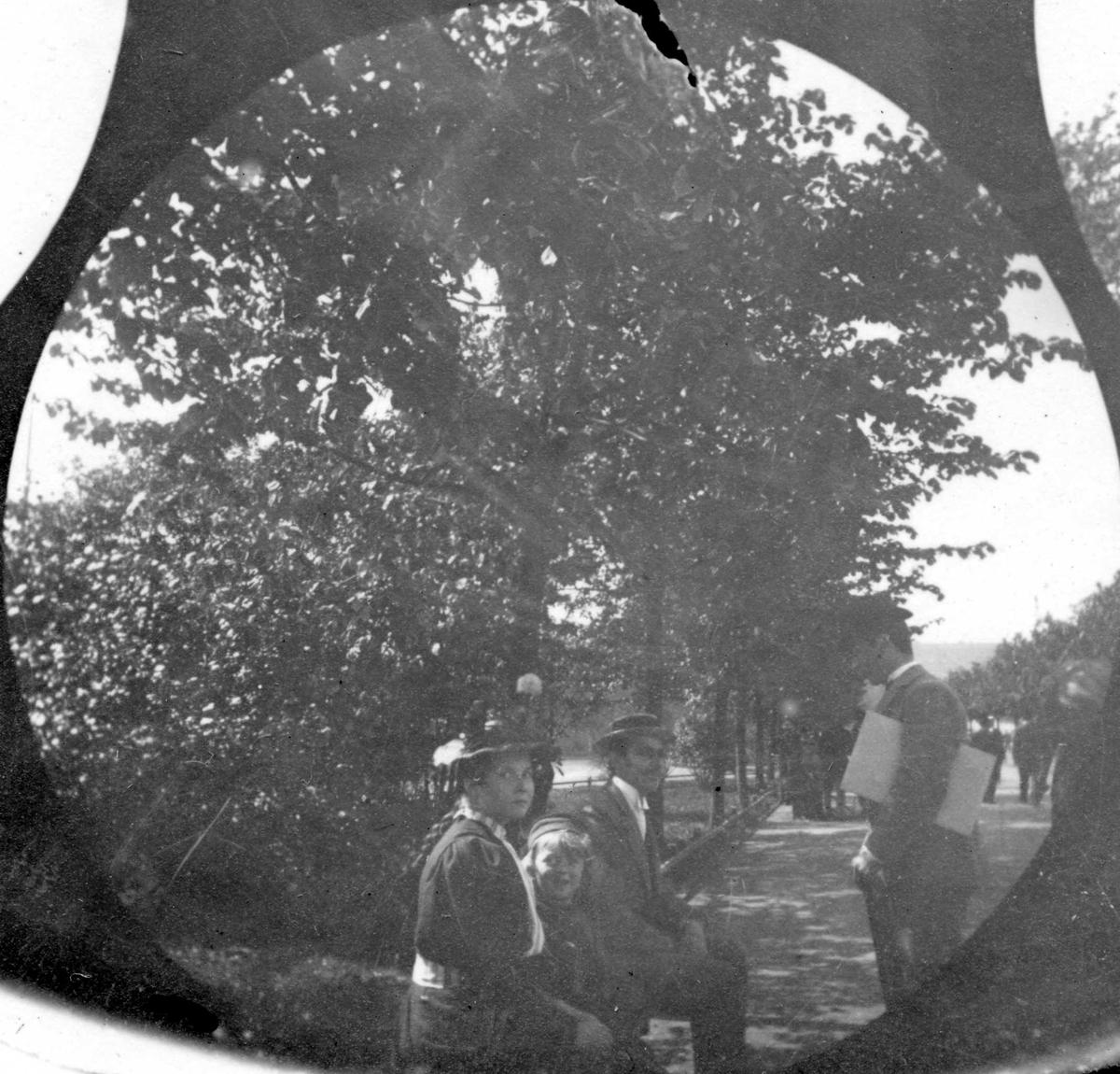 Mann, dame og et barn sitter på parkbenk. Mann står og prater.