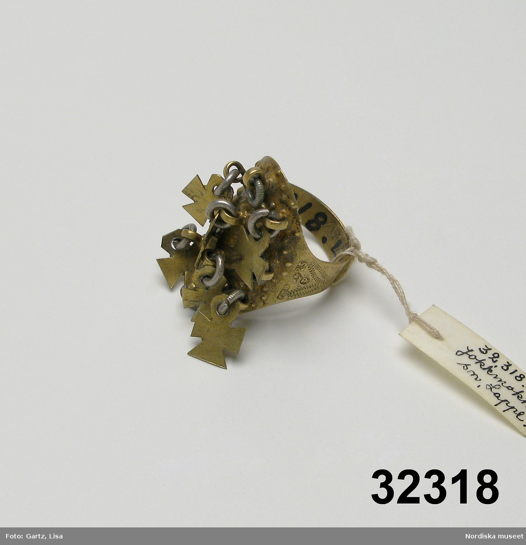 """Huvudliggaren: """"Ring fr. Jokkmokks sn. Af silfver. Märkt: 'M A.'R 5.' 'P'. Ink. af major V. Stål i Stockh. jämte 32.319-32.325. 1/7 1882."""""""