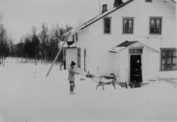 To personer og et reinsdyr utenfor legeboligen Solheim hvor